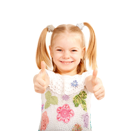 Smiling kid showing thumbs up symbol. Isolated on white background photo