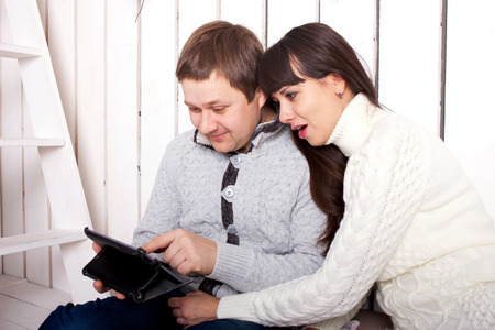 Happy family using a tablet PC. Couple, man and woman reading and sending something in the internet photo
