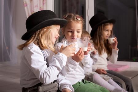 leche de soya: Niños divertidos en sombreros negros beben leche. Foto de archivo