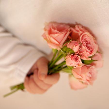 life giving birth: Mano Beb� reci�n nacido con un ramo de flores, peque�as rosas de color rosa. Foto de archivo