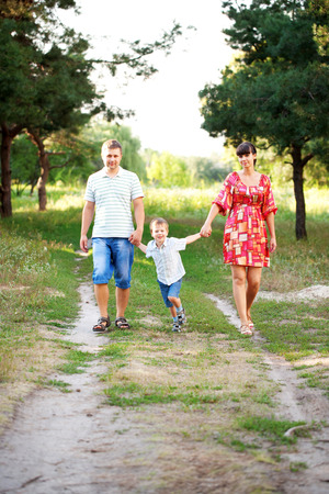 prime adult: Happy family concept. Father, mother and son walking outdoors. Summer holiday. Stock Photo