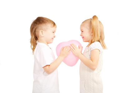 Little children, boy and girl holding pink heart and looking eye to eye. Love and valentine's day concept. Isolated on white  photo