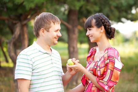 Happy middle aged couple with apple. Summer holiday. Happy family concept. photo