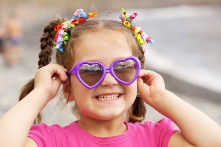 Summer holidays. Funny little girl wearing a sunglasses on the beach.  photo