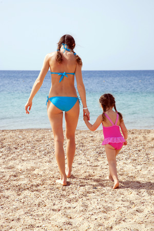 Mother and daughter holding hands and going to swim in the sea on the sandy beach. Rear view. photo