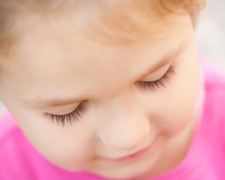 Sad child face close-up. Selective focus on the eyes and eyelashes a kid. Child looking down. photo