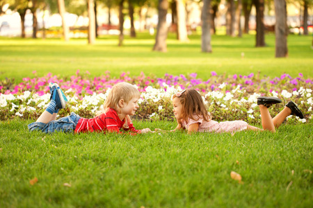 Summer holidays and children happiness. Couple of kids relaxing on the grass. photo