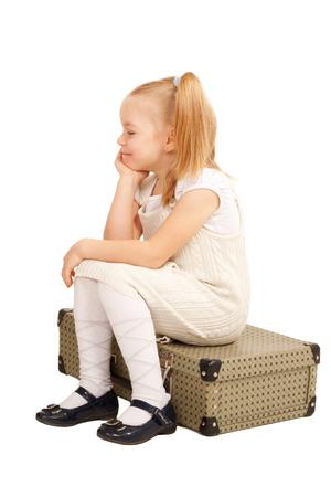 Small traveler girl sitting on a suitcase. Isolated on white background. photo