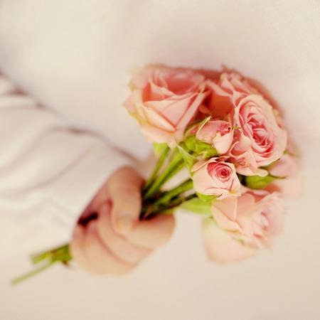 Bebé recién nacido mano que sostiene el ramo de rosas de estilo retro Día de la Madre s, Padre s Day concepto