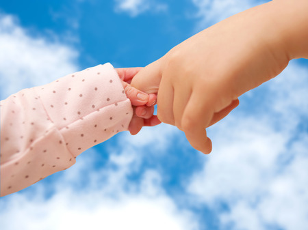 life support: Two children holding hands on sky background. Newborn baby and small kid. Protection, family and support concept. Stock Photo