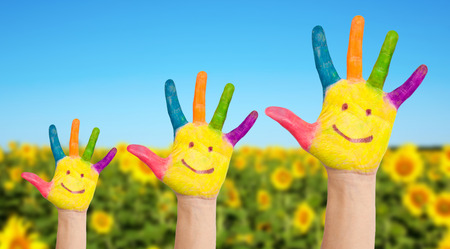 Three colorful painted hands with smiling face of family, mother, father and baby on background of sunflowers field in sunny summer's day. Summer holidays and family concept