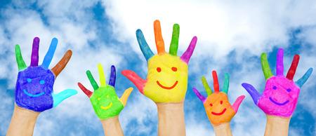 夏の休日、幼年期および家族の概念。幸せな家族の雲と青空の背景に笑顔でカラフルな絵の具で手します。夏の明るい色