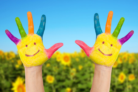 Two smiley hands on a background of field of sunflowers  and blue sky in sunny summer's day. Summer holidays concept.