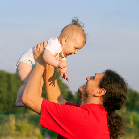 Father and baby playing outdoors. Fathers day, happy family concept. photo