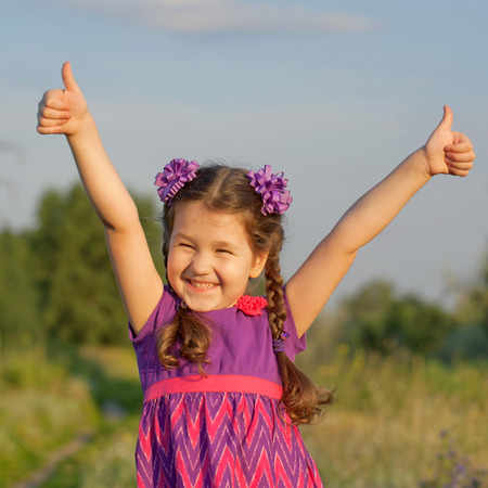 Small child showing thumbs up symbol outdoors photo