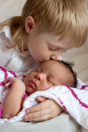 nursing sister: Multiracial family concept. Brother kissing newborn sister. Stock Photo