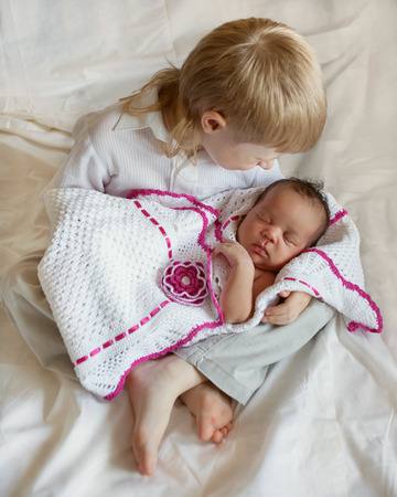 nursing sister: Multiracial family concept. White brother and black newborn sister. Stock Photo