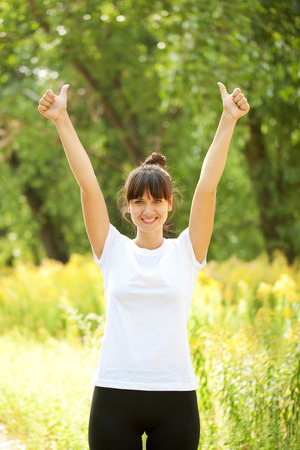 thumbs up woman: Woman in white t-shirt showing a thumbs up sign outdoors. Ready for your text or symbols.