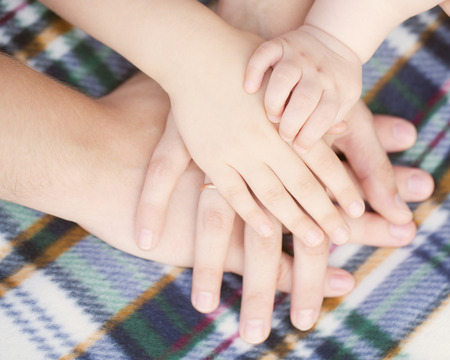 Closeup of baby, child, mother, father hands. Selective focus on infant hand. Unity, support, protection and happiness. Family concept photo