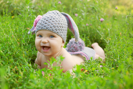Portrait of a baby in the hat like a bunny or lamb of green grass. Happy childhood outdoors. photo