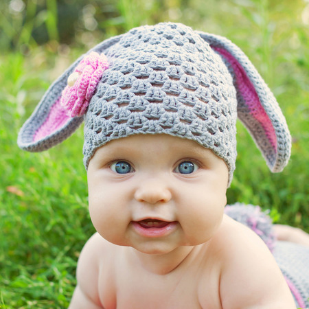 Portrait of a baby in the hat like a bunny or lamb of green grass. Happy childhood outdoors.