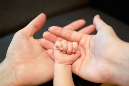 Family concept. Hands of father, mother and newborn baby. Parents holding in the palms a child's hand.