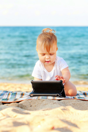 Happy baby with a tablet pc on the beach. Summer holidays concept photo
