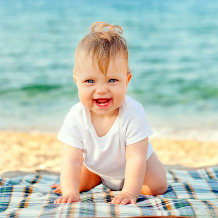 Happy baby on the beach at the seaside. Summer holidays concept