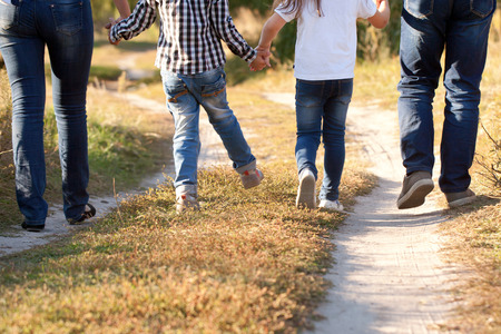 Family feet and legs in jeans. Father, mother, son and daughter walking on the road. Rear view.