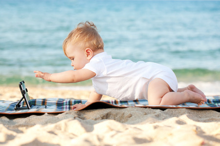 Happy baby with a tablet pc on the beach photo