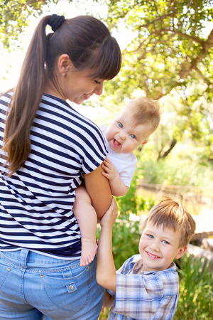 Happy young mother with two kids on a walk, a preschooler and a toddler. photo