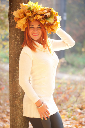 Autumn portrait. Young woman with crown of fall maple leaves photo