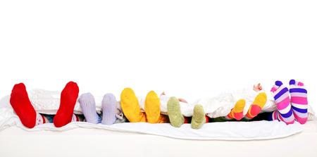 Familie samen slapen. Voeten van vader, moeder en vier kinderen in kleurrijke gebreide sokken op wit bed. Geïsoleerd op een witte achtergrond. Klaar voor uw tekst Stockfoto