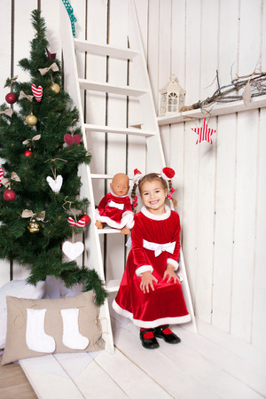 miracle tree: Little kid wearing as Santa Claus sitting near the Christmas tree and awaiting a miracle.