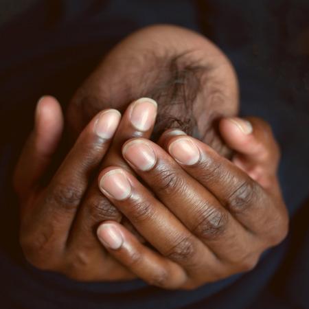 Papa noir et enfant. Père tenant la tête du bébé nouveau-né dans ses paumes. Entretien concept. Banque d'images - 33487916