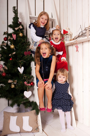 Happy kids laughing near the Christmas tree and waiting for Santa Claus photo