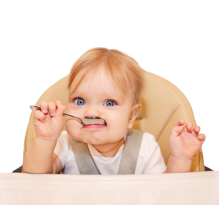 dirty faces: Happy eating baby in a high chair. Isolated on white background. Stock Photo