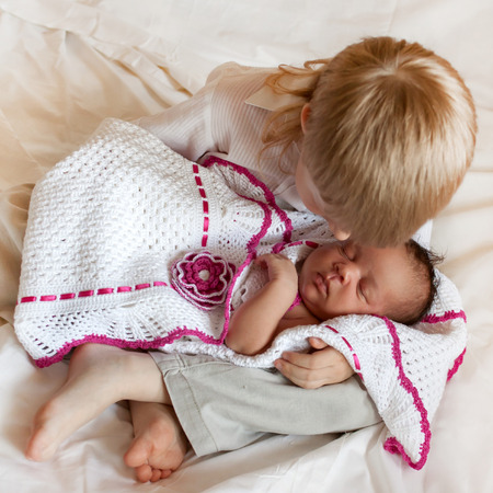 Multiracial family love. White brother and black newborn sister. photo