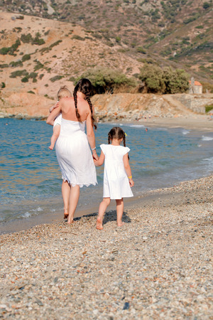 woman back view: Happy family walking on the beach. Mother and two kids, baby and toddler. Rear view Stock Photo