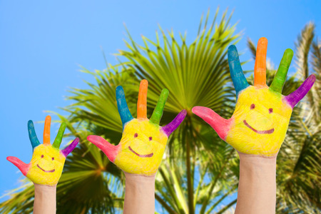 Family hands with smiles against palm and  blue sky background. Summer holidays concept photo