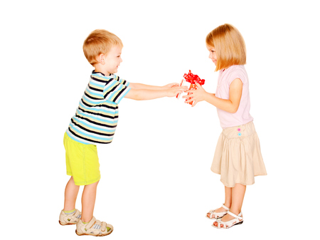 Boy giving to his girl a gift box. Isolated on white background. photo