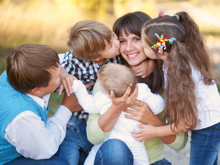 large family: Large family hugging and having fun outdoors. Selective focus on mothers hands and the head of the baby. Son and daughter kissing mother. Happy family concept.