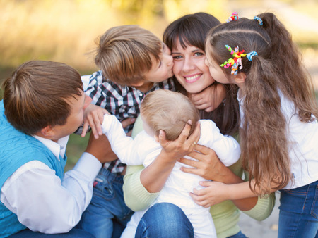 mother kissing daughter: Large family hugging and having fun outdoors. Selective focus on mothers hands and the head of the baby. Son and daughter kissing mother. Happy family concept.