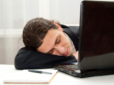 Office worker falling asleep at desk with a laptop and a notebook Stock Photo
