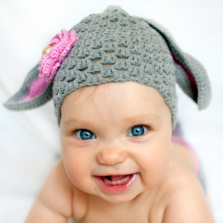 Happy baby in the hat like a bunny or lamb
