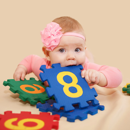 nibbling: Smart baby playing and nibbling figures and numbers on a beige background. Mathematics in infancy.