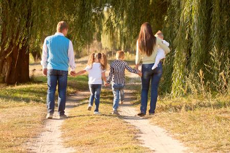 Grote familie wandelen in het park. Achteraanzicht. Familie stropdassen concept.