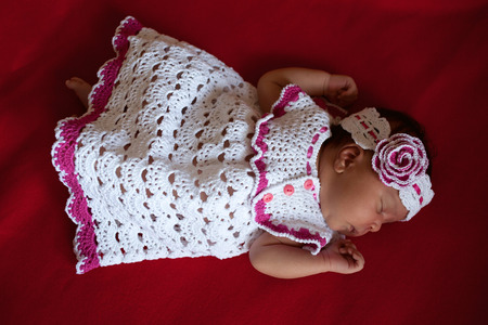 mixed race baby: Black newborn baby in white knitted dress sleeping on a black background.