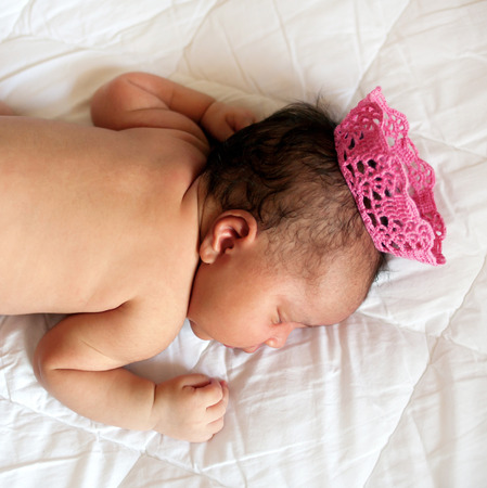 child girl nude: Black small newborn baby sleeping on a bed in a crown, closeup. Stock Photo