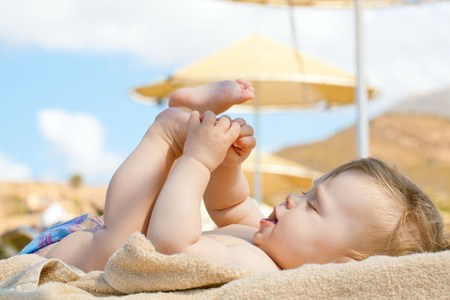 Happy baby resting on the beach sunbed. 8 month old kid lying on sun lounger and playing with her feet. Summer holidays concept.